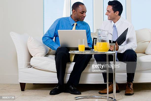 Two businessmen sitting on a couch holding a file and a laptop