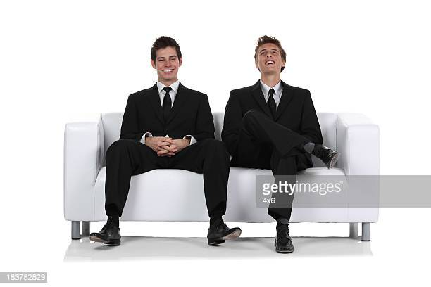 Two businessmen sitting on a couch