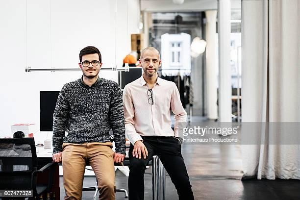 Two businessmen sitting on a desk office room.