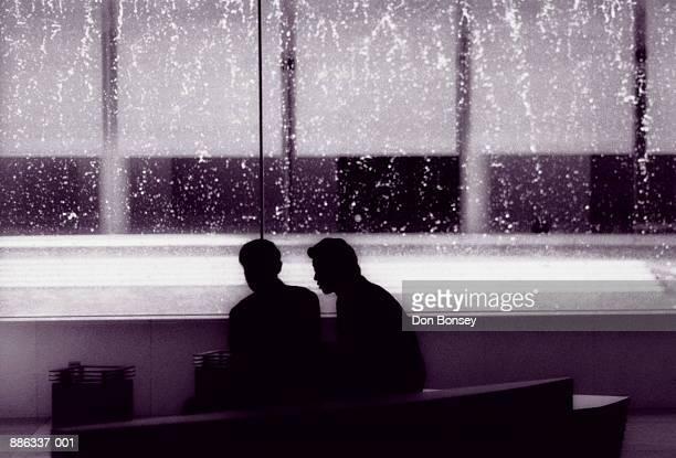 two businessmen sitting on bench, talking, silhouette (b&w) - 若い男性だけ ストックフォトと画像
