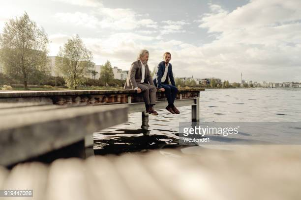 two businessmen sitting on jetty at a lake - familia de dos generaciones fotografías e imágenes de stock