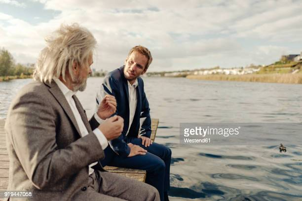 two businessmen sitting on jetty at a lake talking - 後任 ストックフォトと画像