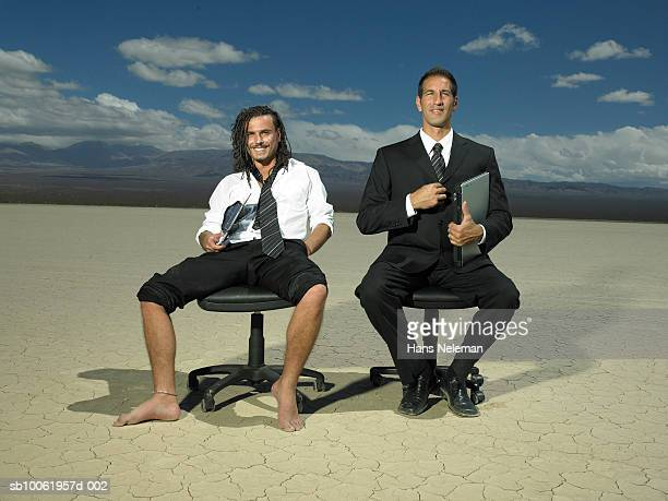 two businessmen sitting on office chair in desert, smiling, portrait - rolled up pants stock pictures, royalty-free photos & images