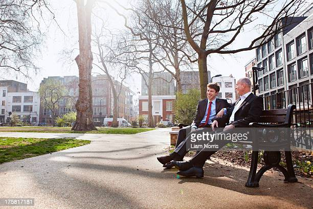 Two businessmen sitting on park bench