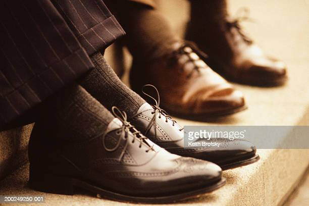 two businessmen sitting on steps, close-up of feet - brown suit stock photos and pictures
