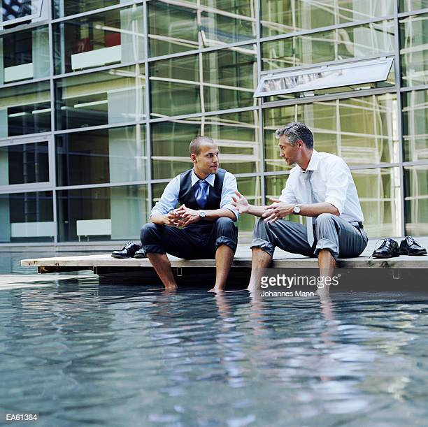 Two businessmen sitting outdoors, feet in pool of water