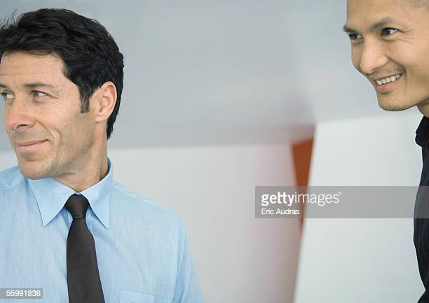 two businessmen, smiling at looking out of frame - out of frame stock pictures, royalty-free photos & images