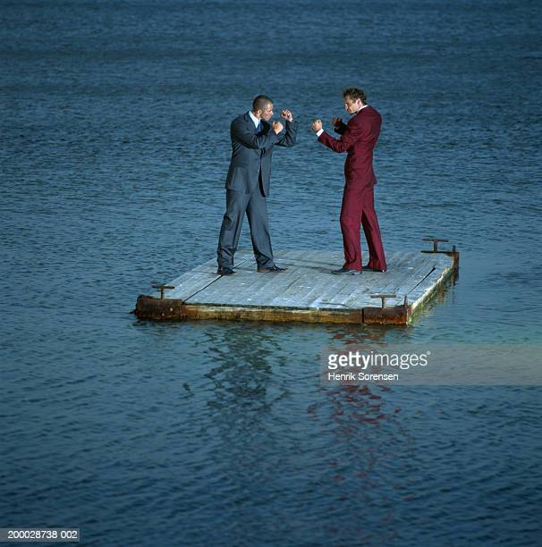 Two businessmen sparring on raft at sea