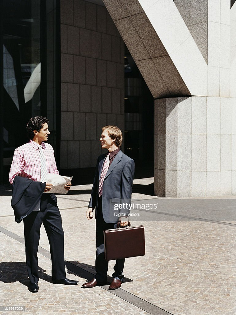 Two Businessmen Stand Outside a Building Talking to Each Other : Stock Photo