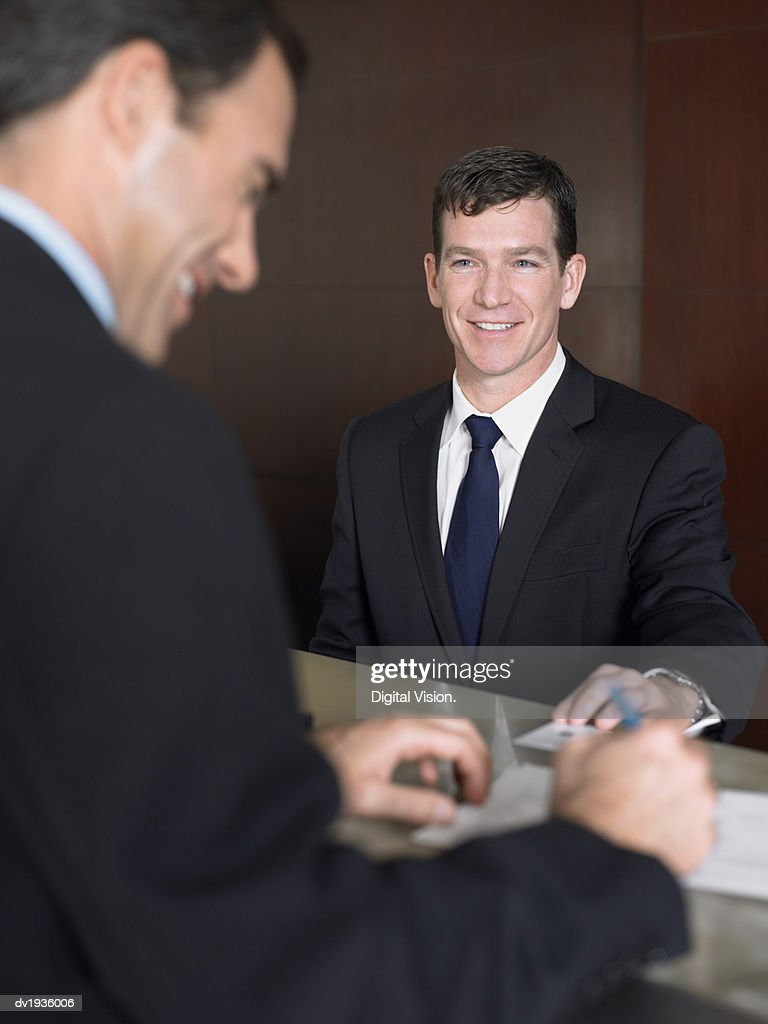 Two Businessmen Stand Smiling at a Reception Desk Signing Documents : Stock Photo