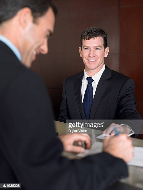 Two Businessmen Stand Smiling at a Reception Desk Signing Documents