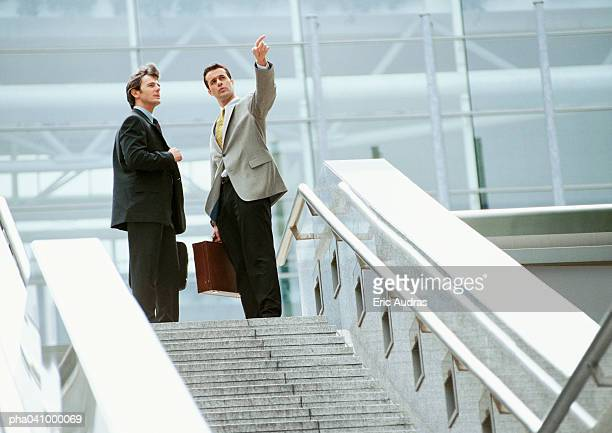 Two businessmen standing at the top of stairs