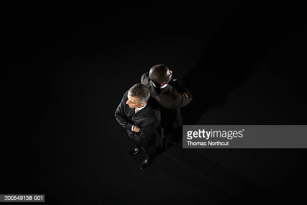 Two businessmen standing back to back, overhead view