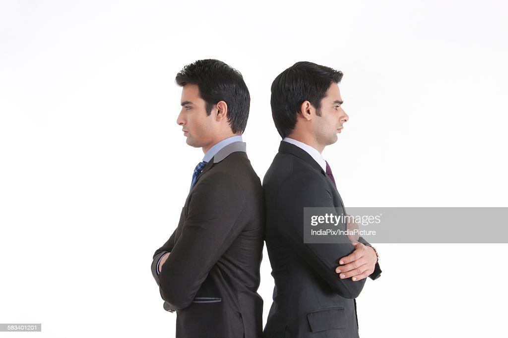 Two businessmen standing back to back : Stock Photo