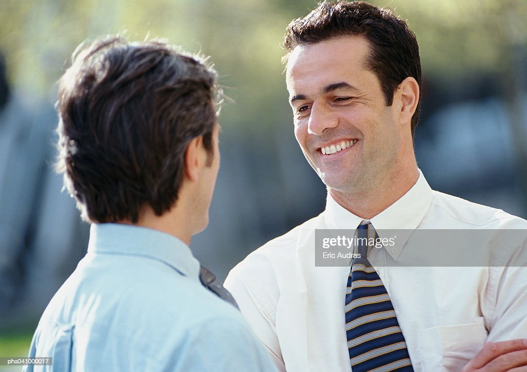 Two businessmen standing face to face, outside : Stockfoto
