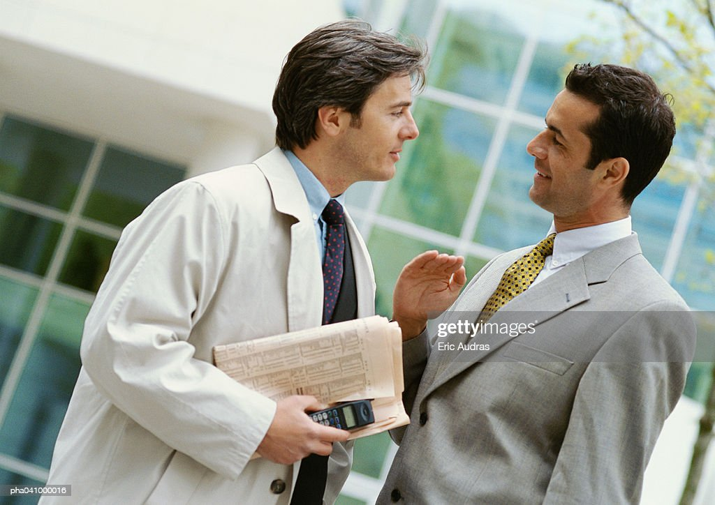Two businessmen standing face to face, side view : Stockfoto