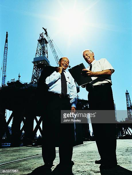 two businessmen standing in a harbour looking down at a clipboard with oil rigs in the background - 隣り合わせ ストックフォトと画像