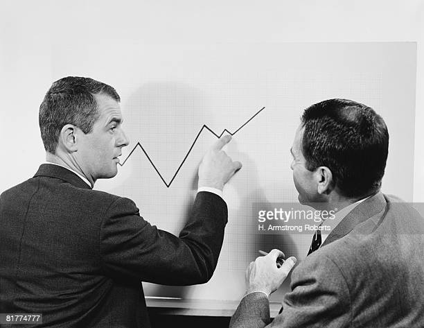 Two businessmen standing in front of chart graphic, pointing to line, peaks and valleys showing growth.