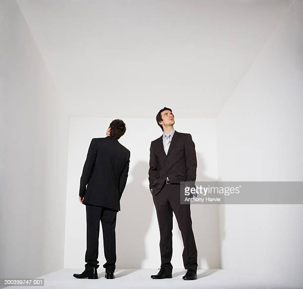 Two businessmen standing in white room