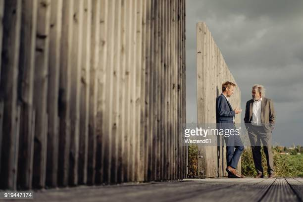 two businessmen standing on boardwalk talking - successor stock pictures, royalty-free photos & images