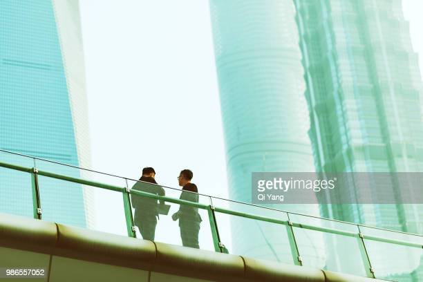 two businessmen standing on bridge and talking - business finance and industry fotografías e imágenes de stock
