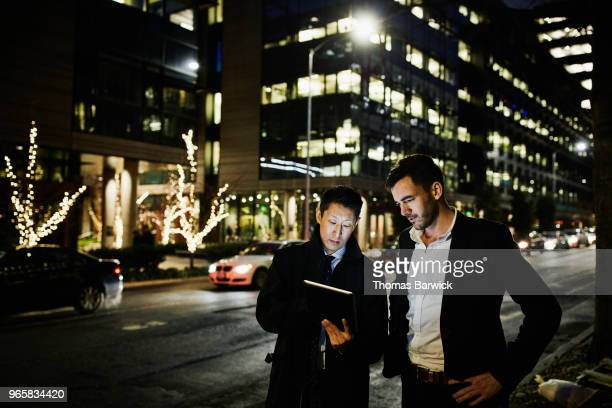 Two businessmen standing on city street at night while looking at data on digital tablet