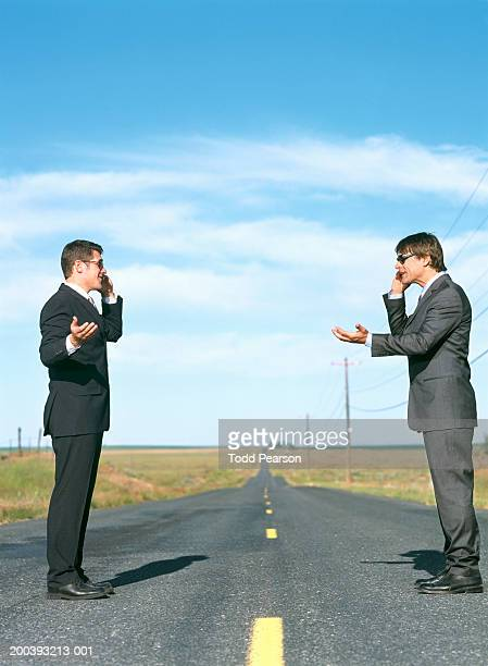 Two businessmen standing on country road, talking on mobile phones