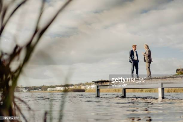 two businessmen standing on jetty at a lake talking - successor stock pictures, royalty-free photos & images