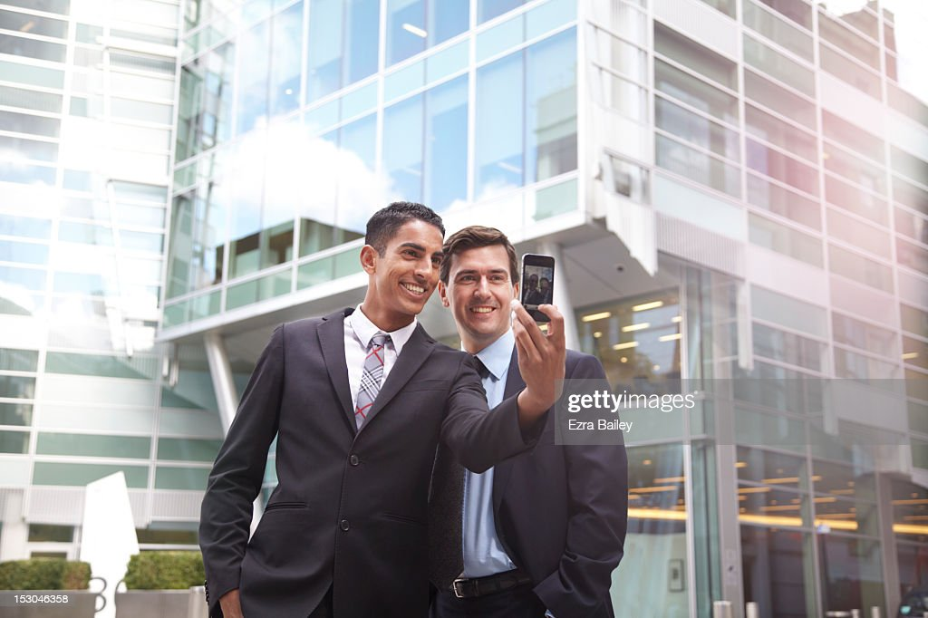 Two businessmen taking a photo of themselves. : Stock Photo