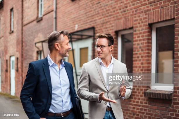 two businessmen talking at brick building - human relationship stock pictures, royalty-free photos & images