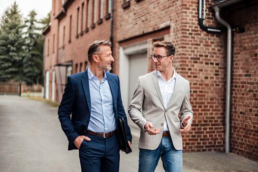 Two businessmen talking at brick building - gettyimageskorea
