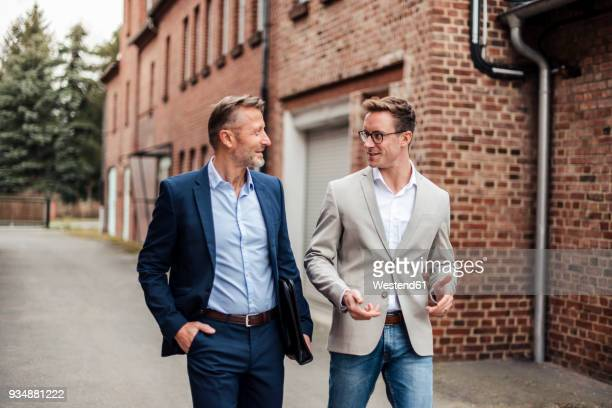 two businessmen talking at brick building - anzug stock-fotos und bilder