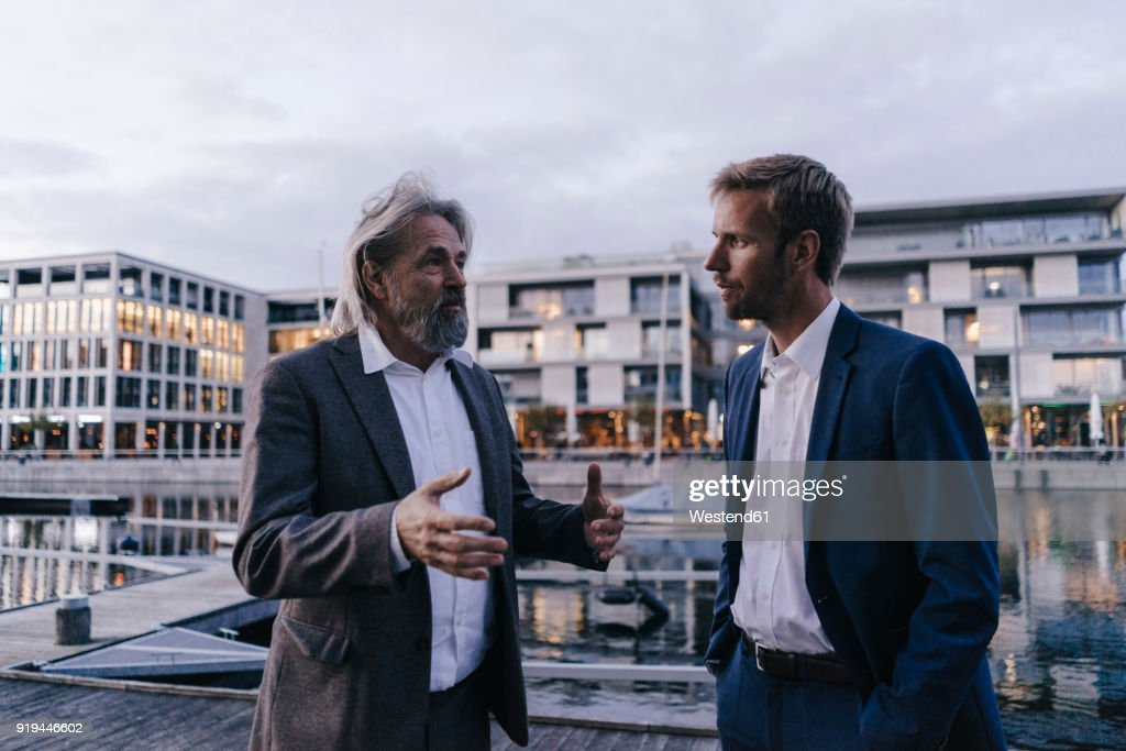 Two businessmen talking at city harbor at dusk : Stock-Foto