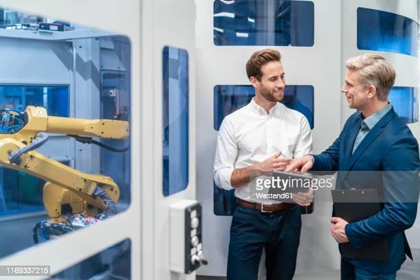 two businessmen talking at robot in a modern factory - rechnerunterstütztes konstruieren stock-fotos und bilder