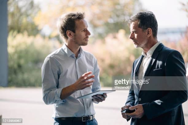 two businessmen talking at the window - finanzen und wirtschaft stock-fotos und bilder