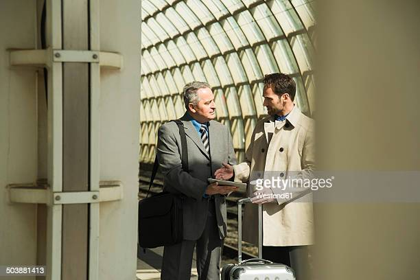 Two businessmen talking at train station