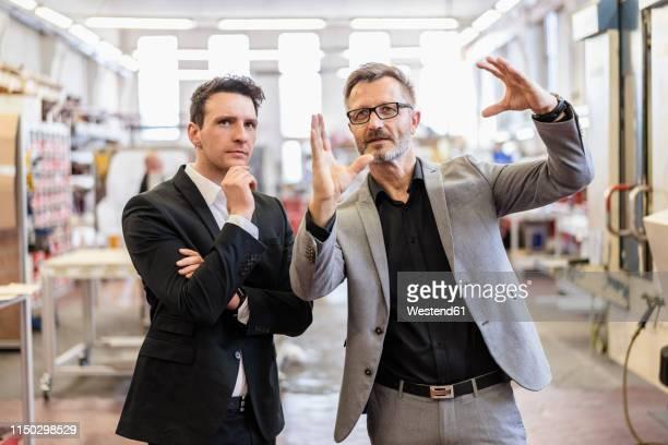 two businessmen talking in a factory - gestikulieren stock-fotos und bilder