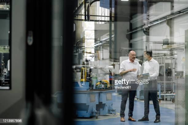 two businessmen talking in a factory - kommunikation themengebiet stock-fotos und bilder