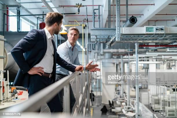 two businessmen talking in a modern factory - herstellendes gewerbe stock-fotos und bilder