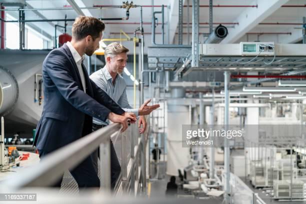 two businessmen talking in a modern factory - finanzen und wirtschaft stock-fotos und bilder