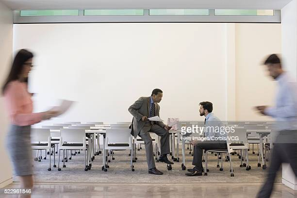 Two businessmen talking in cafeteria