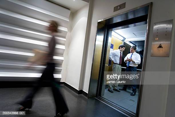 Two businessmen talking in elevator, woman passing (blurred motion)