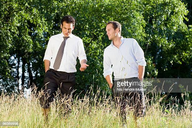 two businessmen talking in field