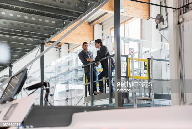 Two businessmen talking in modern factory