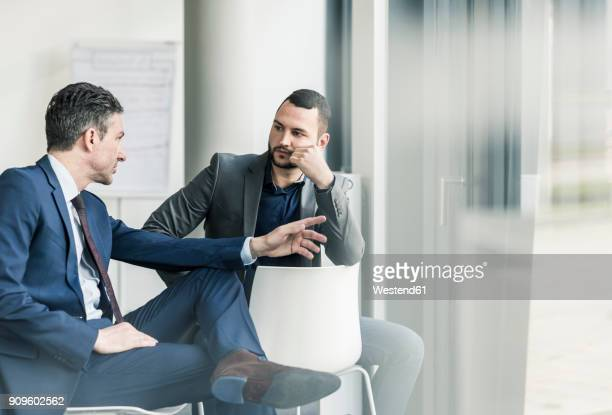 two businessmen talking in office at the window - gespräch stock-fotos und bilder