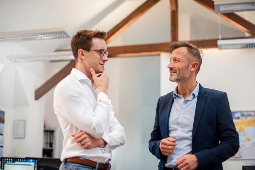 Two businessmen talking in office - gettyimageskorea