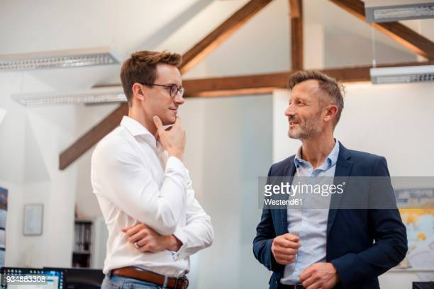 two businessmen talking in office - only men stock-fotos und bilder