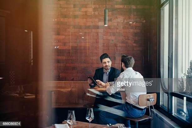 two Businessmen talking in restaurant