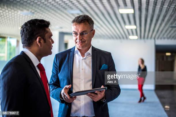 two businessmen talking in the lobby - open collar stock photos and pictures