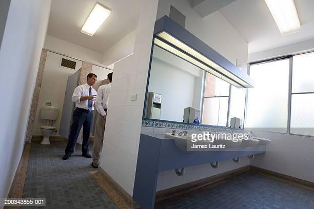 two businessmen talking in washroom - human toilet stock-fotos und bilder